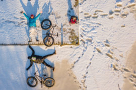 Two people lying in show with fatbikes next to them